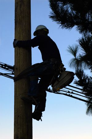 telephone pole: Silhouette of an electrician climbing a newly installed utility pole