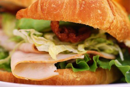turkey bacon: Bacon, lattuga, pomodori, tacchino e avocado sandwich su un cornetto in un bar all'aperto