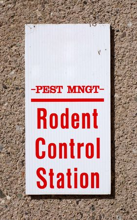 Sign reading Pest Mgmt Rodent Control Station on a wall