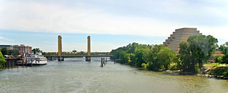 Landmarks of Sacramento, California: Delta King Riverboat, I Street Bridge, Sacramento River and the Ziggurat Pyramid Building.  Photographed from aboard a passenger train stopped on a trestle crossing the river where pedestrian and auto traffic cannot cr
