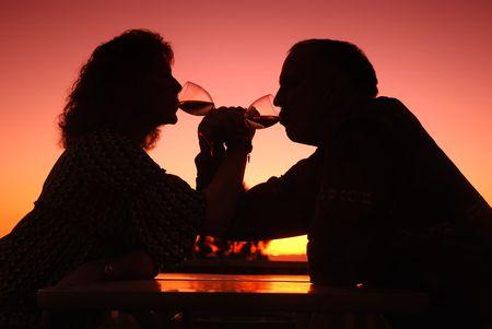 Romantisch paar van middelbare leeftijd drinken van wijn bij zonsondergang