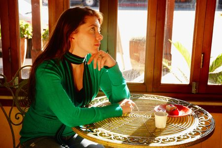 lost in thought: Woman lost in thought at a bistro cafe Stock Photo