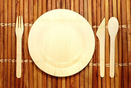 Eco-friendly bamboo plate and silverware on a bamboo place mat -- renewable compostable materials
