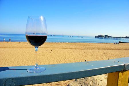 Glas rode wijn in een restaurant dek reling door de oceaan strand