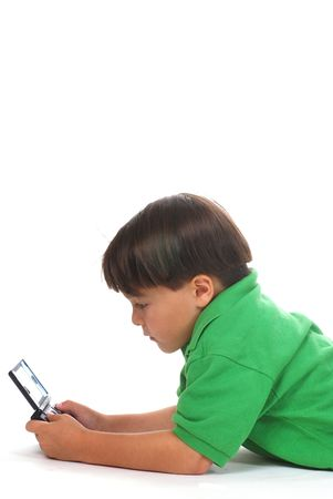 kindergartner: Five year old boy playing with his hand-held video game