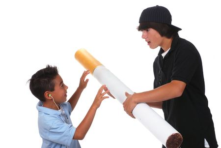 Teenage boy pushes a large cigarette on his younger brother