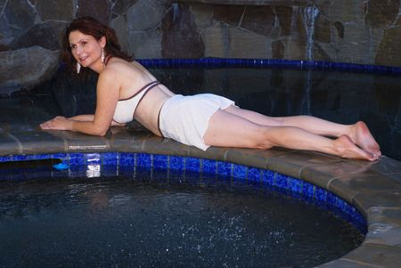 aged: Beautiful middle aged Mediterranean woman relaxing by a pool and hot tub