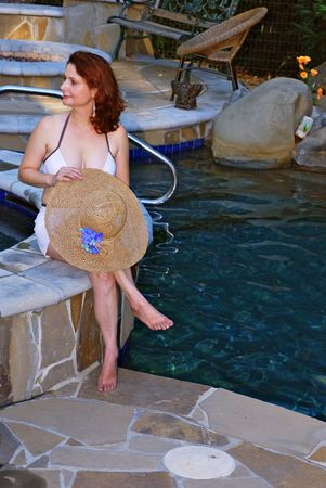 aged: Middle aged woman sitting by pool holding straw hat Stock Photo