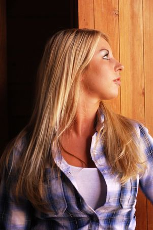 Young adult blonde woman inside a stable on a country farm
