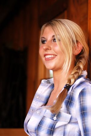 Young adult blonde woman inside a stable on a country farm Stock Photo - 3654762