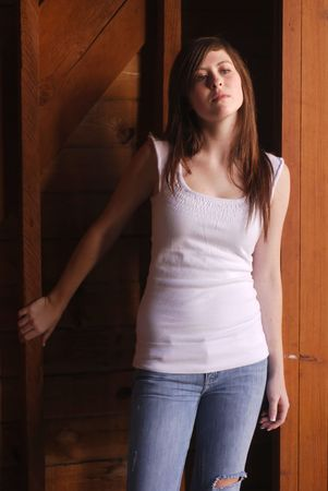 Young adult brunette woman inside a stable on a country farm photo