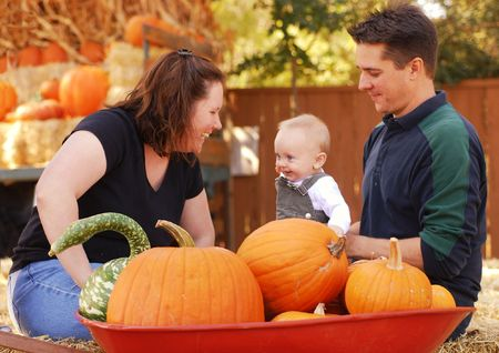 Portrait of a family of three at a pumpkin patch in autumn photo