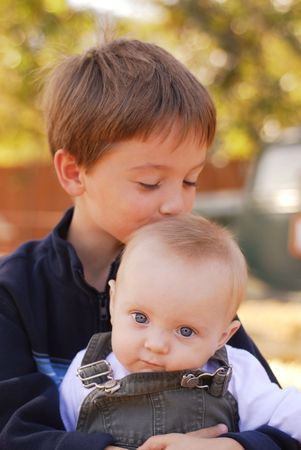 Big brother kissing his little brother on the head at a farm