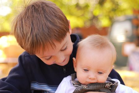 Big brother holding his baby brother at a farm Standard-Bild