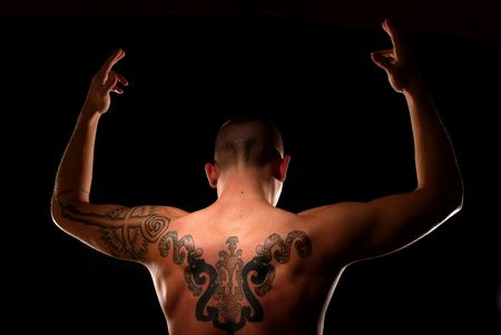 Young man with spiritual tattoos raises his hands toward God photo