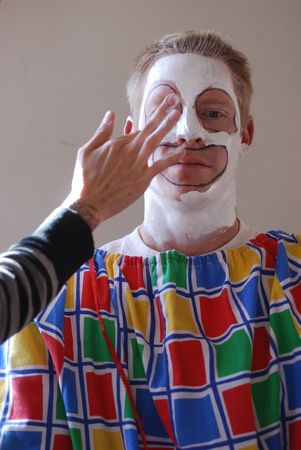 Portrait of a professional clown having makeup applied