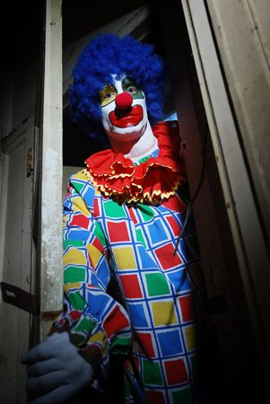 Scary clown lurking around a haunted house