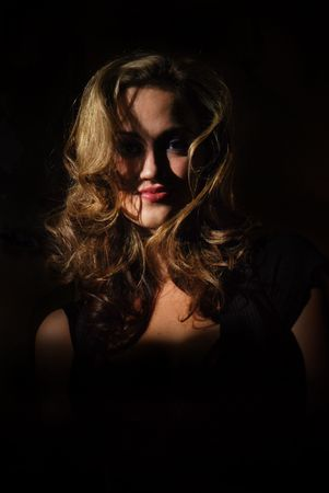Beautiful blonde woman standing in the shadows photo