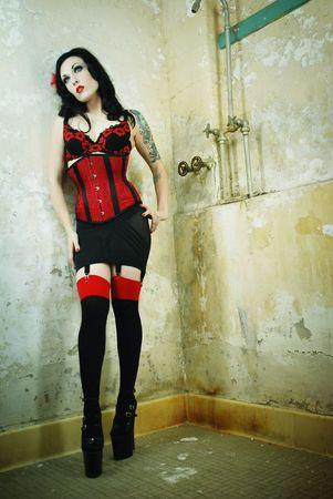赤と黒のランジェリーで服を着て入れ墨を持つ豪華なブルネット