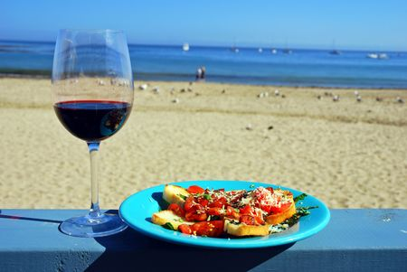 Glass of red wine and plate of fresh bruschetta on a restaurant's deck railing by the ocean beach