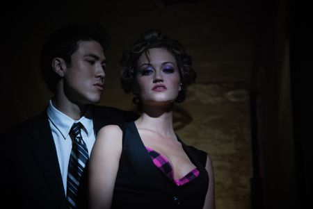 Seedy couple standing in the shadows of a dark hallway