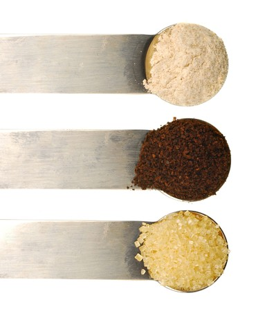 staples: Three kitchen staples in teaspoons isolated on white background