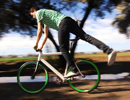 fixed: Joven haciendo trucos de artes fijos en su bicicleta Foto de archivo