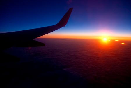 View of sunrise above cloudy horizon from airplane