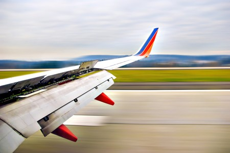 Airplane wing open upon landing on runway in motion Stock Photo