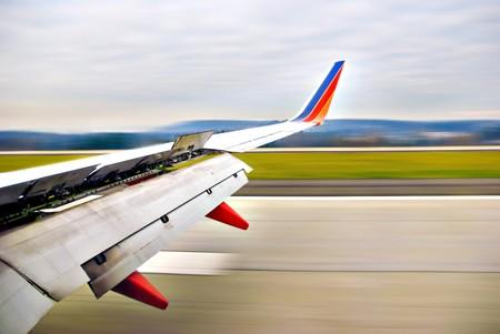 Airplane wing open upon landing on runway in motion Standard-Bild