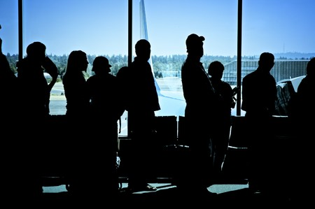vacationers: Travelers standing in line at the airport waiting to board an airplane