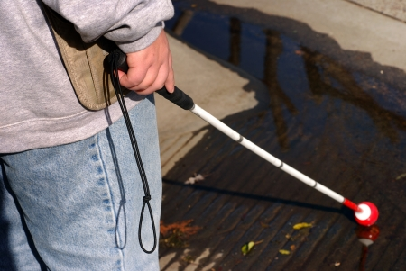 Blind woman finds a puddle with her white cane at a curb cut photo