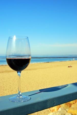 Glass of red wine on a restaurant's deck railing by the ocean beach Standard-Bild