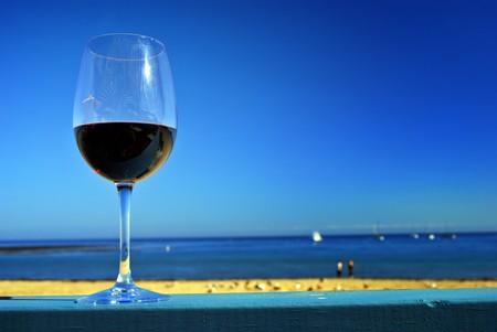 杯在餐馆的甲板栏杆的红葡萄酒由海洋海滩