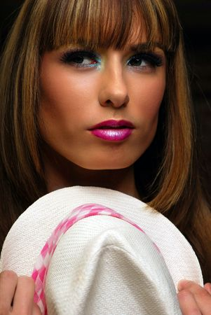 Young brunette woman wearing pink and white fedora hat photo