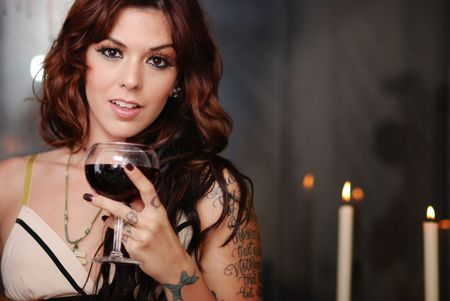Beautiful young brunette with glass of red wine and candles Stock Photo - 4855032