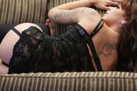Young tattooed woman wearing black lingerie on sofa photo