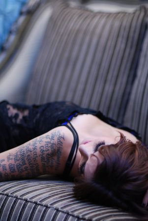Young tattooed woman wearing black lingerie resting on sofa photo
