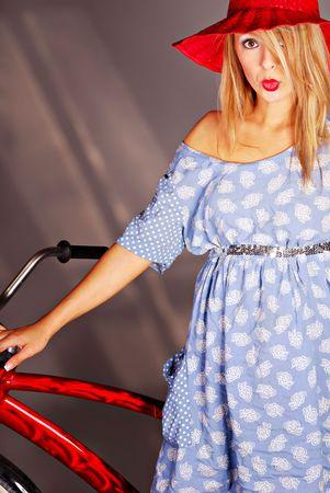 Blonde teenage girl wearing hat standing behind red bicycle photo