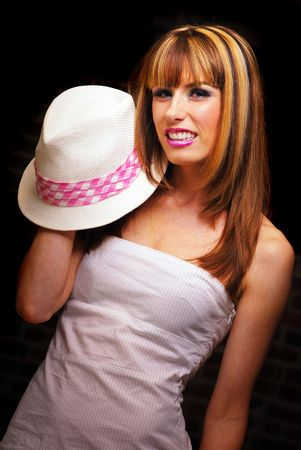 Young brunette woman wearing pink and white fedora hat