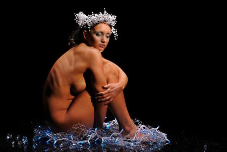 Nude woman surrounded by snow and Christmas lights on black background