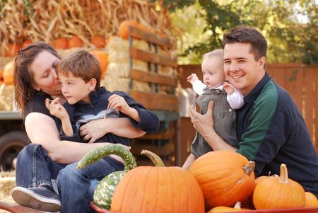Portrait of a family of four at a pumpkin patch in autumn photo