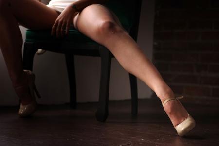 beine spreizen: Frau sitzt im Stuhl mit Beine öffnen sich