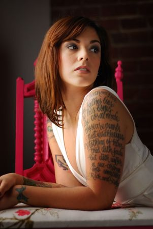 Young tattooed woman with green wooden chair photo
