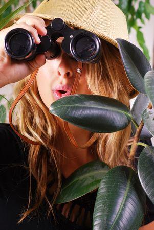 jungle girl: Teenage girl wearing safari hat hiding in the jungle Stock Photo