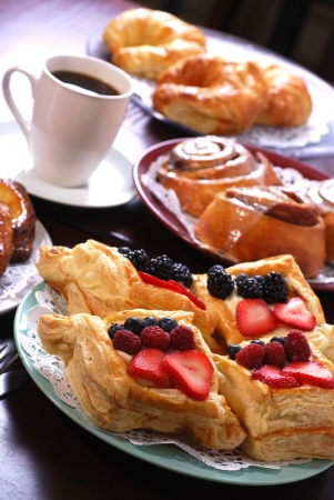 danish: Plates full of assorted pastries with coffee in a bakery