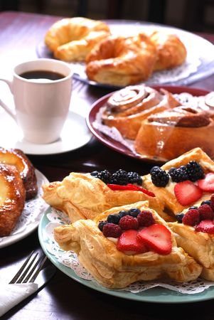 pastry: Plates full of assorted pastries with coffee in a bakery