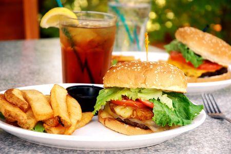 té helado: Burger Teriyaki con grandes papas a la francesa en un restaurante al aire libre Foto de archivo