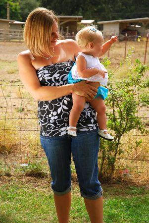 Moeder en haar baby op een paard boerderij Stockfoto