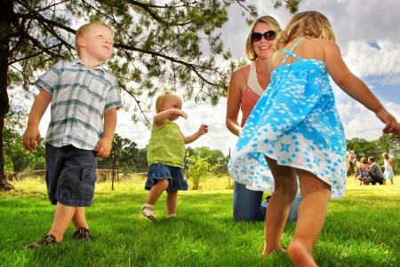 the yards: Familia jugando en la hierba en una granja de caballo Foto de archivo